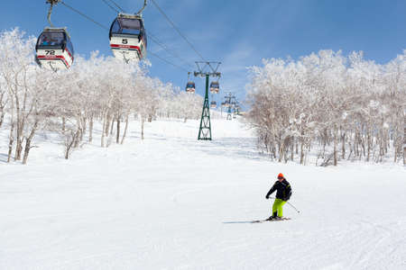 NISEKO, JAPAN - MARCH 9 : A man skis past a gondola lift in the Niseko Annupuri ski resort on 9th March 2012. Niseko is a large ski resort located on Mount Annupuri on Hokkaido Island. Japan.