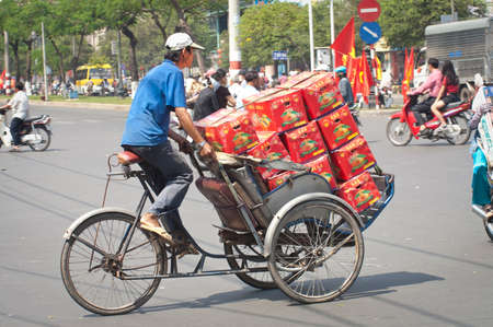 overloaded: Ho Chi Minh City, Vietnam - February, 6 2005: Man pedals a trishaw, loaded with boxes on a road in Ho Chi Minh City