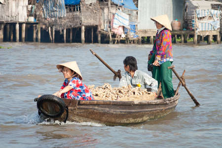 Can Tho, Vietnam - February, 1 2005: Three people on a small wooden boat transport baskets of fresh ginger stems to the floating market at Cần Thơ on the Mekong Delta, Vietnam