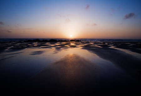 Sun sinks behind horizon at Porthtowan, Cornwall with colourful reflections in the pools of water on the beach  photo