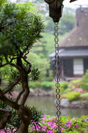 A Japanese rain chain or kusari-doi which is a traditional rain drainage system found in many Japanese temples and houses  The chain directs rain water from the roof gutters to the drains  Stock Photo