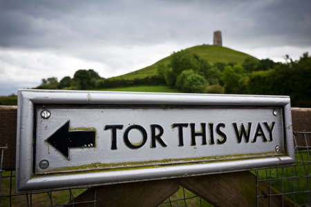Sign pointing the direction to Glastonbury Tor, Somerset, England  Selective focus on sign and St Michael