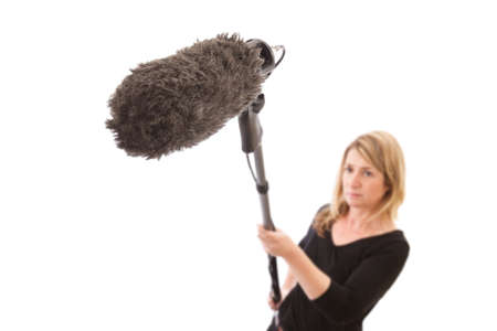 Woman holding a microphone boom against a white background  Selective focus on the furry microphone  windshield
