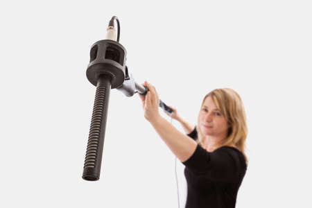 Woman holding a microphone boom against a plain background  Selective focus on the microphone and microphone mount