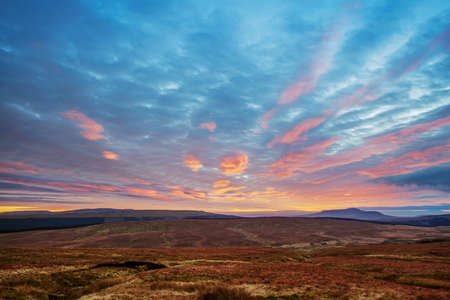Yorkshire Dales: Sunset view across moorland to the Pennines in the Yorkshire Dales  The distinctive, plateaued peak of Ingleborough, one of the famous three peaks, can be seen on the horizon