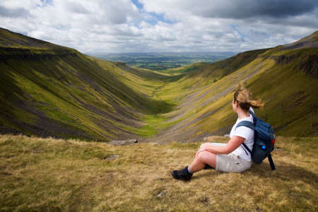 away from it all: On a windy day a walker sits enjoying the view from a Cumbrian beauty spot called High Cup Nick in England, UK
