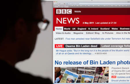 BATH, UK - MAY 4, 2011 A silhouetted man views the latest stories on the BBC News website on 4th May 2011  The headlines are dominated by the death of Osama Bin Laden which happened on 2nd May 2011  Stock Photo - 25119634