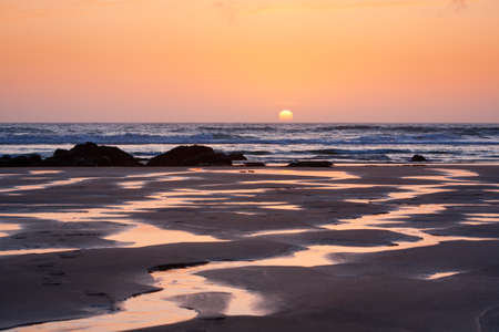 Bright orange setting sun reflects in the meandering rivulets of water on Porthtowan Beach in Cornwall, UK photo