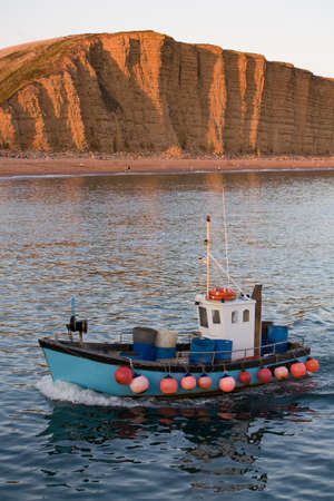 Fishing trawler sails into West Bay harbour with the cliffs of the Jurassic coast