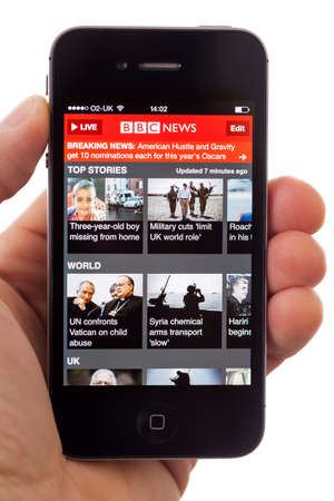 BATH, UK - JANUARY 16, 2014  A man s hand holding an Apple iPhone 4s displaying the front page of the BBC News App, against a white background