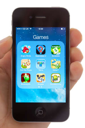 BATH, UK - JANUARY 17, 2014  A hand holding an Apple iPhone 4s which is displaying a selection of well known games including the best selling app Angry Birds  Shot in close-up with a white background