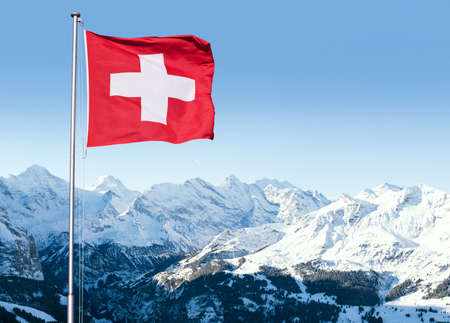 The flag of Switzerland fluttering in the wind with the Bernese Alps in the background, Grindelwald, Switzerland