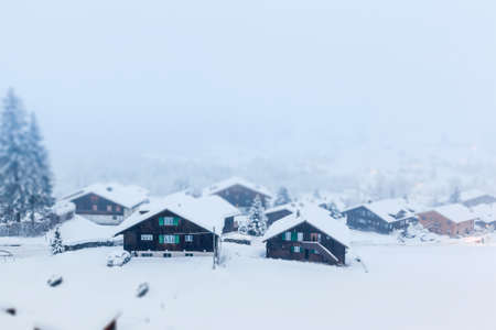 postproduction: Traditional wooden houses in Grindelwald, Switzerland during heavy snow fall  Treated with a tilt-shift effect in post-production