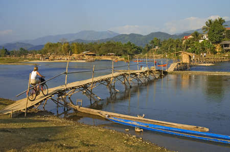 rickety: Cyclist crossing rickety wooden bridge in Vang Vieng, Laos.