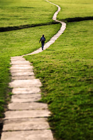 Yorkshire Dales: Woman walking on a long flagstone pathway snaking through a grassy field in the Yorkshire Dales, England, UK  Focus vignette added in post-production