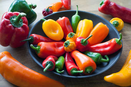 A mix of sweet and hot chilli peppers in a bowl and on a kitchen chopping board photo