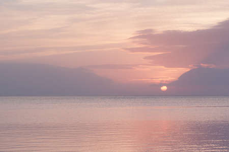 pastel shades: Sun sets over calm sea with soft pink pastel shades Stock Photo