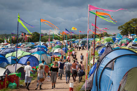 GLASTONBURY, UK - JUNE 27, 2014   People walking through a  camping area with colouful flags at Glastonbury Festival 2014