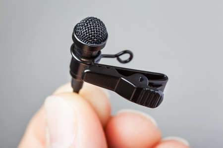Close-up of a hand holding a tie-clip microphone with a plain background
