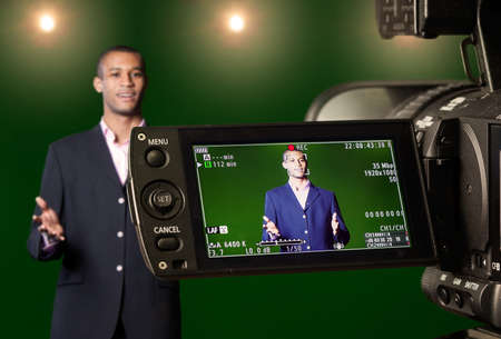 Television presenter in a green screen TV studio, seen through the LCD display of a digital camera. Selective focus on the viewfinder. Stockfoto