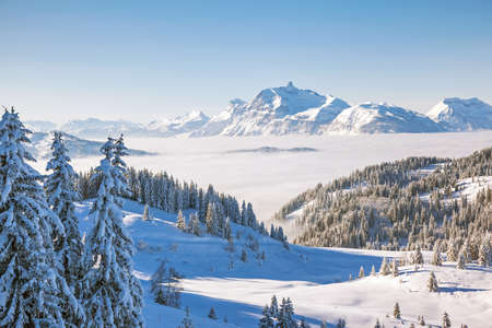 soleil: Winter view from the slopes of Les Gets in the Portes du Soleil ski area, France. The distinctive peak of Pointe Percee in the Aravis mountain range can be seen in the background. Stock Photo