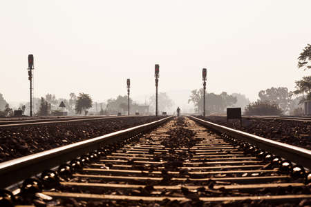 distant: A distant, silhouetted man walking on the railway track near Khajuraho train station in India.