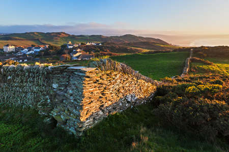 devon: Corner of a dry stone wall in a North Devon field with views of Mortehoe village  and Woolacombe bay in the background Stock Photo