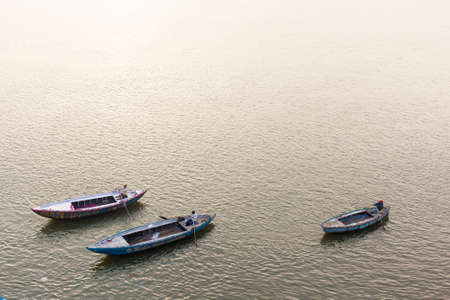 sculling: VARANASI, INDIA - JANUARY 05, 2015 : Three men rowing boats on the Ganges river. Editorial