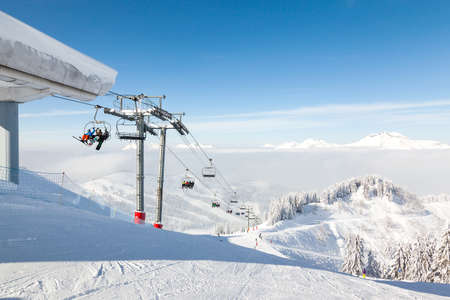 boarders: MORZINE, FRANCE - FEBRUARY 06, 2015: Skiers and snow boarders on the Ranfoilly Express chair lift at the top of Le Ranfoilly peak in the the Les Gets ski area in the Portes du Soleil ski area.