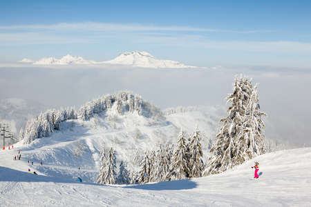 boarders: MORZINE, FRANCE - FEBRUARY 06, 2015: Skiers and snow boarders on Le Ranfoilly mountain peak in Les Gets ski resort in the Portes du Soleil ski area.