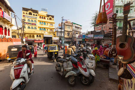 locals: UDAIPUR, INDIA - JANUARY 16, 2015 : Busy street scene in Jagdish Chowk, a central town square in Udaipur filled with mopeds, rickshaws, locals, tourists, hotels, shops and restaurants.