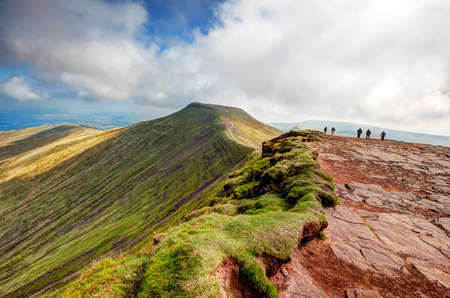 beacons: BRECON, WALES - SEPTEMBER 07, 2014 : People walking towards the peak of Pen y Fan from the top of Corn Du in the Brecon Beacons.