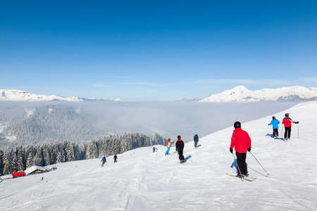boarders: MORZINE, FRANCE - FEBRUARY 07, 2015: Skiers and snowboarders on La Combe piste in Morzine resort, part of the Portes du Soleil ski area. Editorial