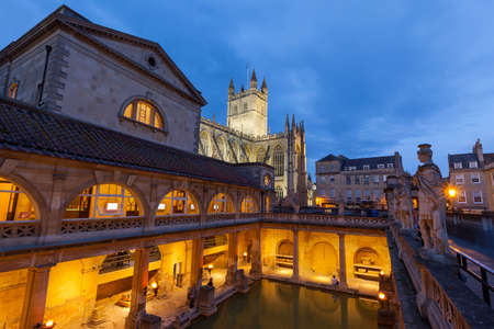 The Roman Baths and Bath Abbey at night in Bath, England. The Baths and Abbey are popular tourist attractions in the centre of the historic British city.