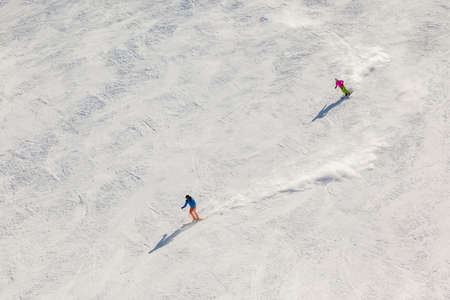 ski run: Two skiers on a steep black ski run with trails of snow dust behind them.