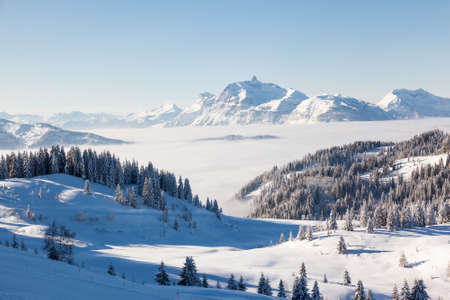 gets: Winter view from the slopes of Les Gets in the Portes du Soleil ski area, France. The distinctive peak of Pointe Percee in the Aravis mountain range can be seen in the background. Stock Photo