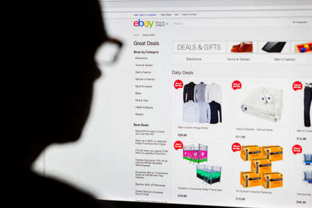 ebay: BATH, UK - SEPTEMBER 14, 2015: Close-up of the Ebay  homepage displayed on a LCD computer screen with the silhouette of a mans head out of focus in the foreground.