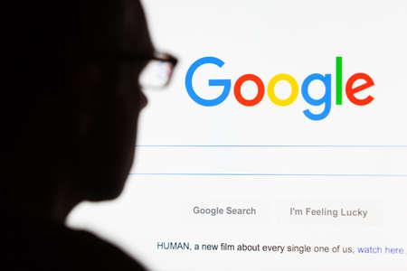 Bath, Wielka Brytania - 12 września 2015: Close-up z wyszukiwarki Google.com głównej wyświetlanej na ekranie LCD komputera z sylwetka głowy mężczyzny nieostry na pierwszym planie. Publikacyjne