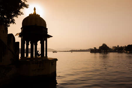 Man sitting looking at his mobile phone under a domed pavilion beside Pichola Lake in Udaipur, Rajasthan Stock Photo