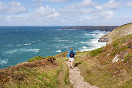 south west coast path: Woman walking the South West Coast Path near Mawgan Porth in Cornwall, UK. Stock Photo