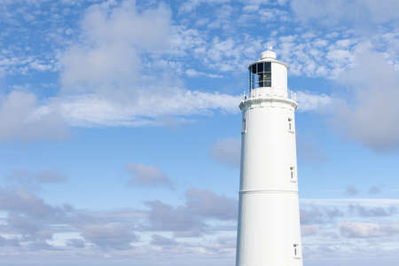 landscape format: White lighthouse against a bright summer sky. Landscape format with space for text. Stock Photo