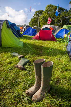 british weather: A pair of muddy wellington boots at a British music festival campsite. Shallow depth of field with selective focus on the boots.