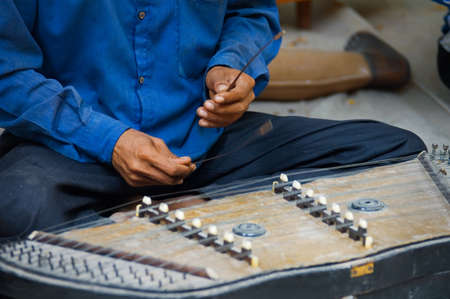 paraplegic: Cierre de las manos de v�ctimas de minas terrestres tocar un instrumento musical tailand�s Khim en atracci�n tur�stica en Siem Reap, Camboya. Foto de archivo