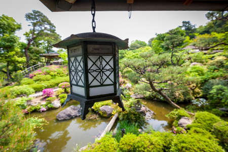 tr: A traditional metal lantern hanging from a veranda which overlooks a beautiful Japanese garden