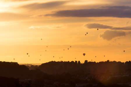 fiesta popular: Silhouetted hot air balloons at sunset over the Avon Valley near Bath during the mass ascent, part of the Bristol Balloon Fiesta on 13th August 2016.