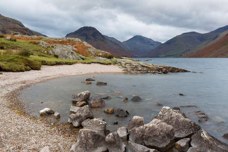cumbria: Rocky Beach on the Shore of Wast Water in Cumbria, UK. Water blurred by long exposure. Stock Photo