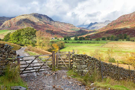 langdale pikes: Wooden gateway in Little Langdale, the Lake District, England.The Langdale Pikes can be seen in the background. Stock Photo