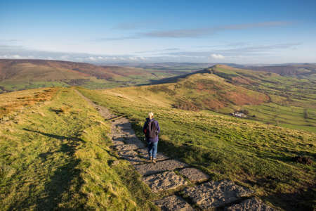 uk: Woman walking the stone path from Mam Tor to Hollins Cross near Castleton in the Peak District, Derbyshire, UK. Stock Photo
