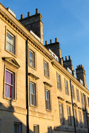 roof windows: Top section of a row of stone houses in a terrace in Bath, UK.