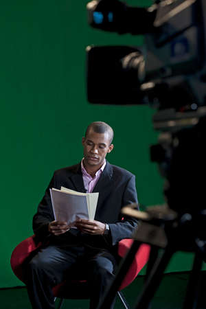 sit on studio: A TV Presenter sits reading through scripts in a green screen TV Studio